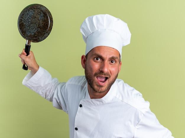 Woedende jonge blanke mannelijke kok in uniform van de chef-kok en dop die koekenpan opheft en naar camera kijkt schreeuwend geïsoleerd op olijfgroene muur