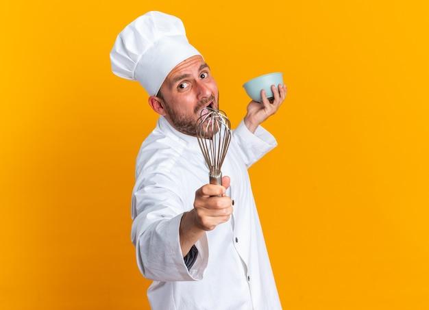 Woedende jonge blanke mannelijke kok in uniform van de chef-kok en pet staande in profielweergave kijkend naar camera die zich uitstrekt garde en kom geïsoleerd op oranje muur met kopieerruimte