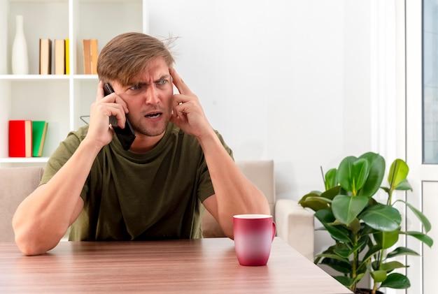 Woedende jonge blonde knappe man zit aan tafel met kopje praten over de telefoon en zetten hand tempel kant in de woonkamer kijken