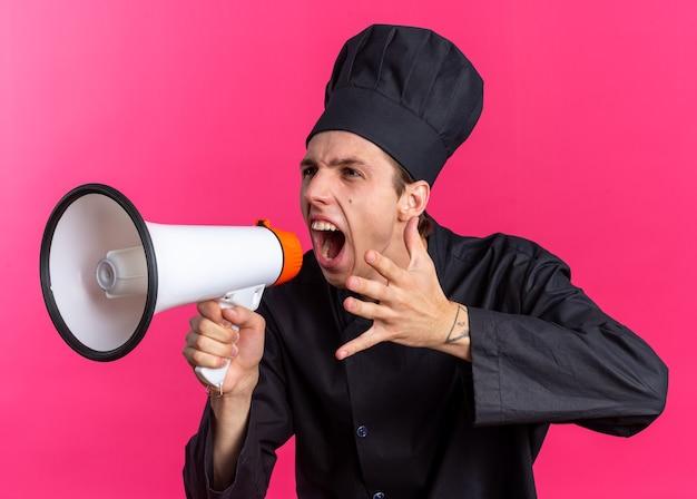 Woedende jonge blonde mannelijke kok in chef-kok uniform en pet kijkend naar kant schreeuwend in luidspreker die hand in de lucht houdt geïsoleerd op roze muur