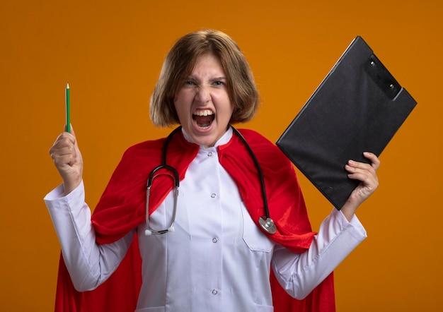 Woedende jonge blonde superheldenvrouw in rode cape die artsenuniform en stethoscoop met klembord en potlood dragen die voorzijde bekijken die op oranje muur wordt geïsoleerd