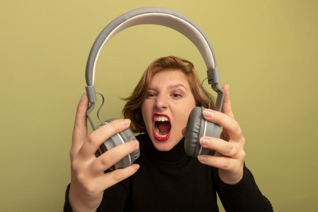 Woedende jonge blonde vrouw die een koptelefoon vasthoudt en kijkt die schreeuwt op een olijfgroene muur