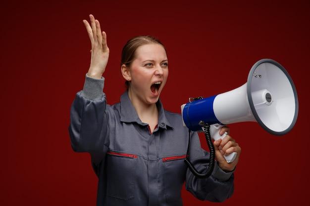 Woedende jonge blonde vrouwelijke ingenieur die eenvormig draagt die kant bekijkt die hand opheft die in luide spreker schreeuwt