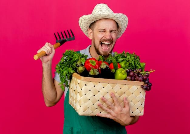 Woedende jonge knappe slavische tuinman in uniform en hoed met mand met groenten en hark schreeuwen geïsoleerd op karmozijnrode muur