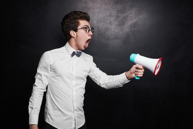 Woedende jonge mannelijke regisseur in nerdy outfit en bril luid schreeuwen naar megafoon