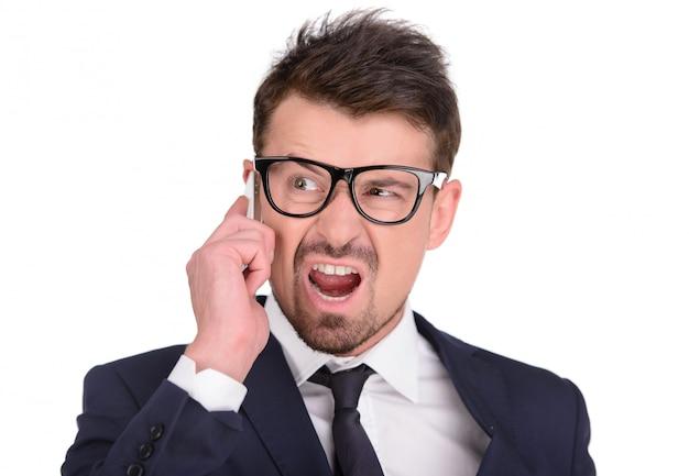 Woedende jonge zakenman die een mobiele telefoon houdt.