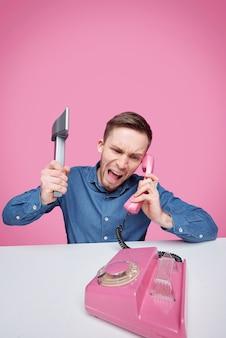 Woedende jongeman met bijl die woede uitdrukt terwijl hij in roze plastic telefoonhoorn schreeuwt en over iets klaagt