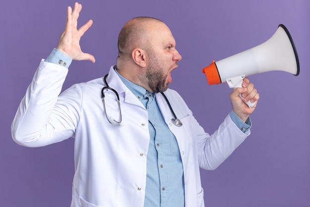 Woedende mannelijke arts van middelbare leeftijd die een medisch gewaad en een stethoscoop draagt en naar de zijkant kijkt terwijl hij schreeuwt in een luidspreker die zijn hand opsteekt