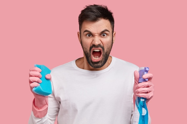 Woedende ongeschoren man draagt blauwe dweil en wasmiddel, gekleed in witte kleren, is boos op vrouw die hem huis laat schoonmaken