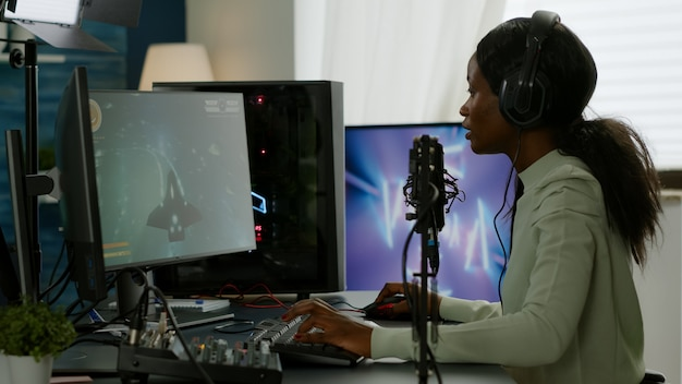 Woedende pro afro-amerikaanse gamer die in microfoon praat voor ruimteschieter die videotoernooi verliest. virale videogames streamen voor de lol met koptelefoon en toetsenbord voor online kampioenschap.