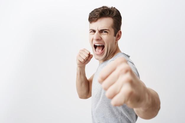 Woedende verontwaardigde blanke man schreeuwt van woede, fronst zijn gezicht, houdt vuisten en gaat zichzelf verdedigen in de strijd tegen criminelen. het wanhopige donkere haar van de europese kerel toont zijn kracht, balt vuisten.