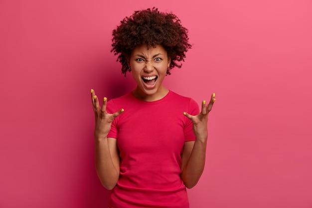 Woedende vrouw schreeuwt van woede, gebaart boos, verliest zijn geduld, geïrriteerd door iets, haat iemand, draagt een casual t-shirt, poseert tegen een roze muur. negatieve emoties, gevoelens