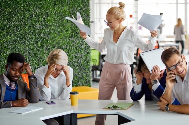 Woedende vrouwelijke directeur ontevreden over het werk, schreeuwt ze tegen medewerkers met papieren