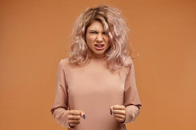 Woedende, woedende jonge vrouw met volumineus haar, vuisten gebald en brullend, haar woede uitend