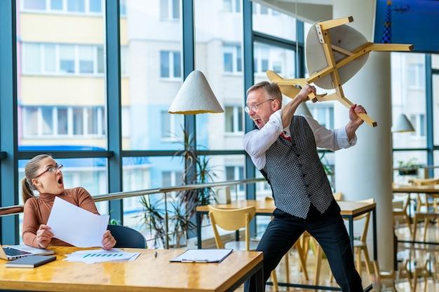 Woedende zakenmanschreeuw naar vrouwelijke werknemer. proberen te slaan met een stoel. gekke mannelijke baas schreeuwt tegen schuldige stagiair, geeft de schuld aan fouten, ceo beschuldigt vrouwelijke werknemer van bedrijfsfalen of slechte resultaten.