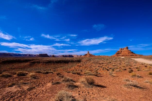 Woestijn met gedroogde struiken in de buurt van een onverharde weg met kliffen in de verte op een zonnige dag