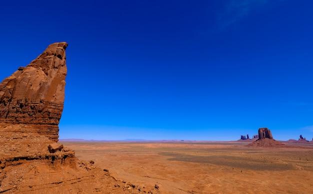 Woestijn met kliffen en droge ingediend met heldere blauwe hemel