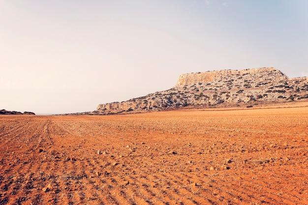 Woestijn op een berg of heuvelachtergrond. geploegd veld voor landbouw. rode aarde. landbouw werk. leeg veld zonder mensen.