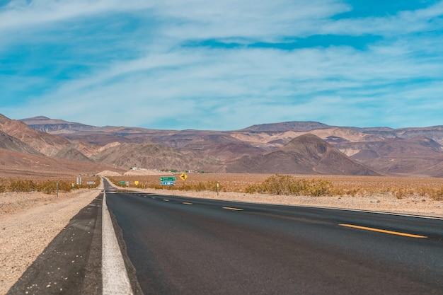 Woestijn schilderachtige weg in death valley met bergachtergrond californië verbazingwekkend panorama van de woestijn