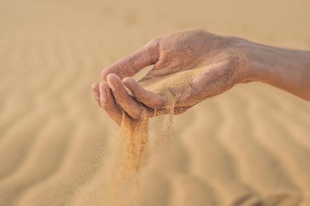 Woestijn, zand blaast door de vingers van een mannenhand