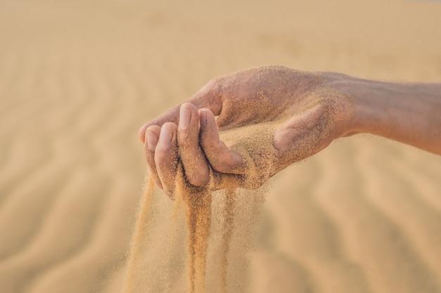 Woestijn, zand puft door de vingers van de hand van een man