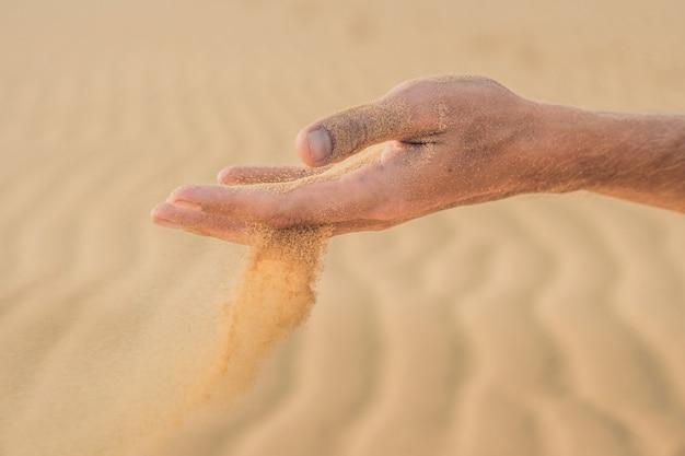 Woestijn, zand puft door de vingers van de hand van een man.
