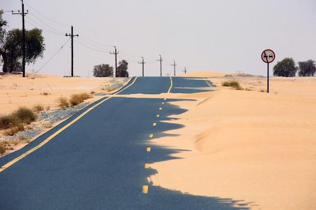 Woestijnweg met zandheuvel en bord over eenrichtingsverkeer