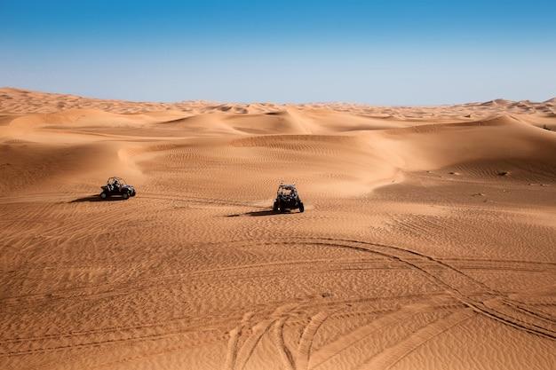 Woestijnzandduinen van dubai met twee quad-buggy's
