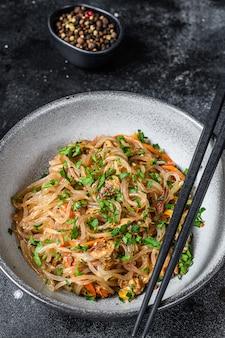 Wok hete aziatische cellofaannoedels met kippenvlees. zwarte tafel. bovenaanzicht.