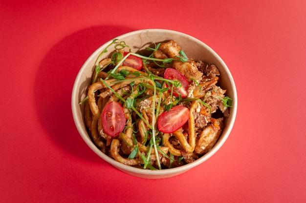 Wok met eiernoedels, kip, carb en pikante wortelen in een romige currysaus. in een maaltijdbezorgingsbord. detailopname. uitzicht van boven. geïsoleerd.