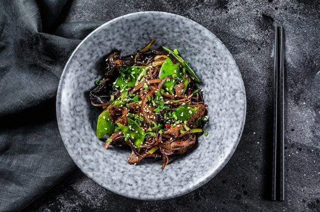 Wok. soba roerbaknoedels met rundvlees en groenten. zwarte achtergrond. bovenaanzicht