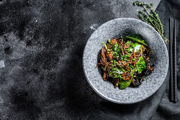 Wok. soba roerbaknoedels met rundvlees en groenten. zwarte achtergrond