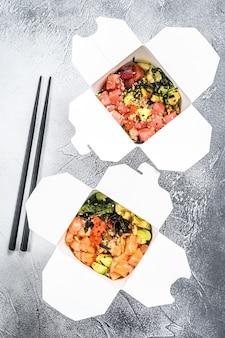 Woknoedel in kartonnen doos met groenten en vis