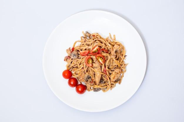 Wokvoedsel op een witte keramische plaat is lekker en vers met saus op een lichte geïsoleerde achtergrond