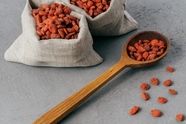 Wolfberries in kleine doekzakken en houten lepel, die op grijze achtergrond worden uitgespreid.