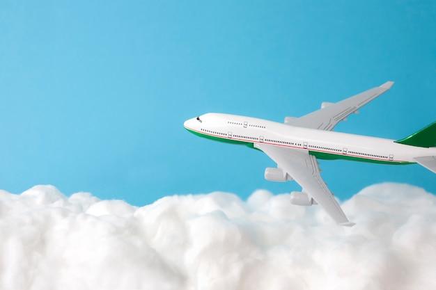 Wolk gemaakt van watten met modelvliegtuig op hemelsblauwe achtergrond