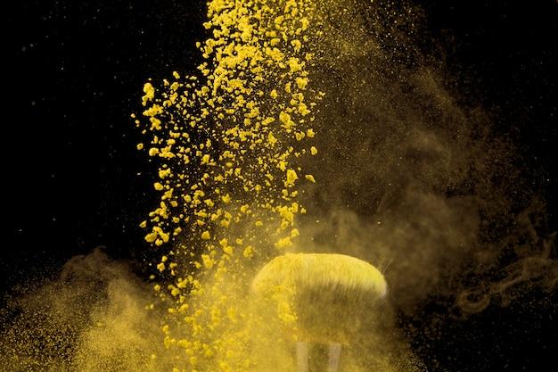 Wolk van gele make-up poeder en penseel op donkere achtergrond