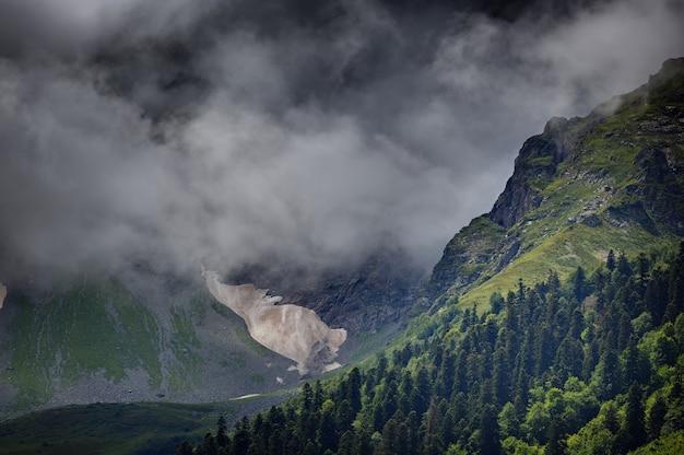Wolken boven de toppen van de rotsachtige bergen begroeid met bomen. gefotografeerd in de kaukasus, rusland.