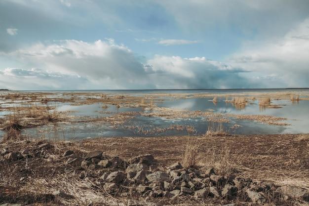 Wolken boven het meer met droog gras.