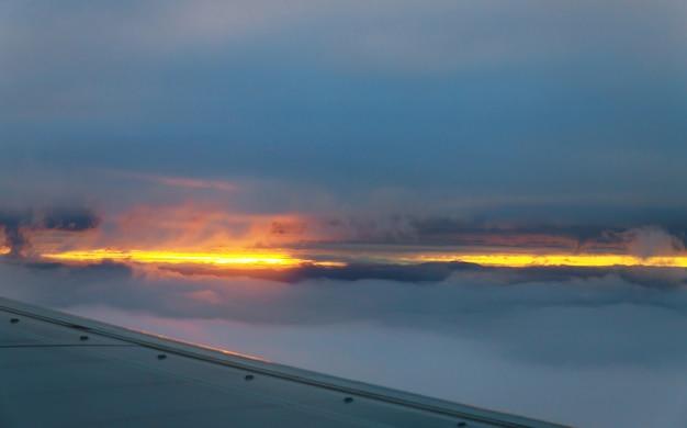 Wolken en hemel zoals gezien door venster van een vliegtuig bij zonsondergang