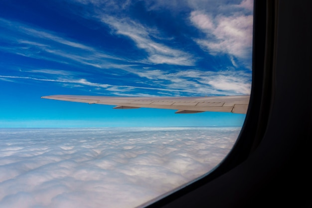 Wolken en lucht en vliegtuigvleugel gezien door het raam van een vliegtuig