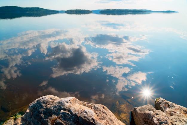 Wolken en zon met weerspiegeling in het water op het meer