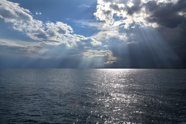 Wolken en zonnestralen boven de zee.