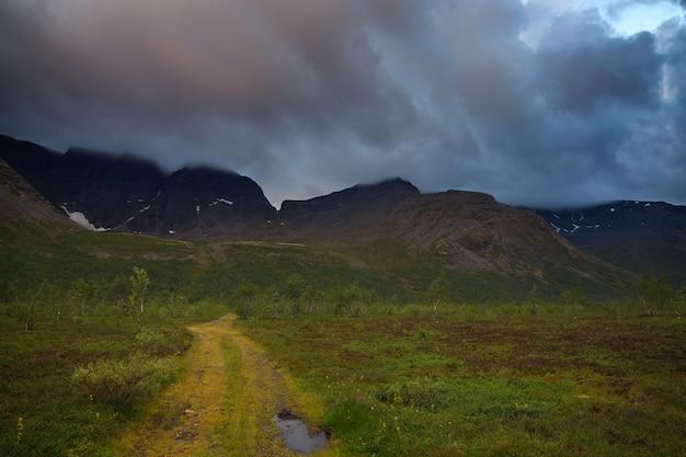 Wolken in de lucht boven de bergen verlicht door de zon bij zonsondergang.