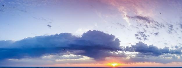 Wolken in de lucht, zonsopgang of zonsondergang, panorama. fel oranje zonlicht verlicht de avondlucht.