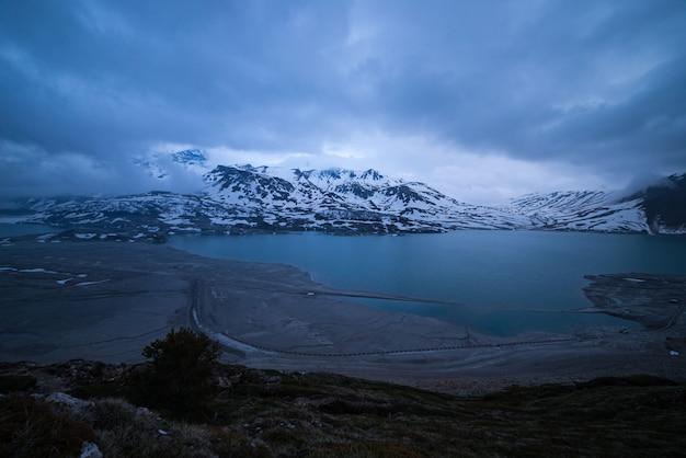 Wolken in de schemering blauwe uur, meer en besneeuwde berg, koude winter, fjord nord landschap