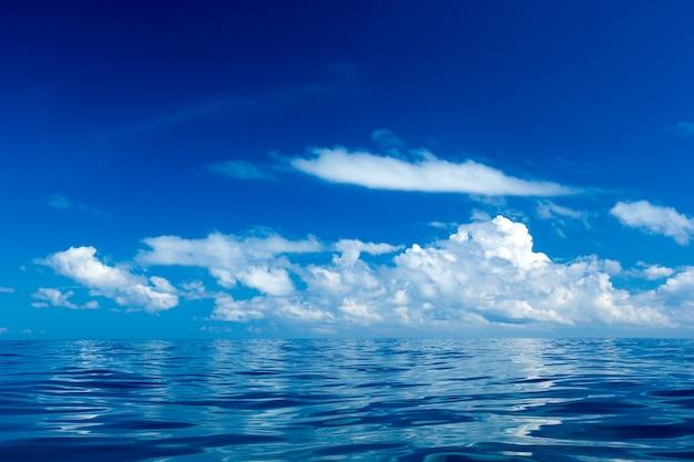 Wolken op blauwe hemel boven kalme zee met zonlicht reflectie