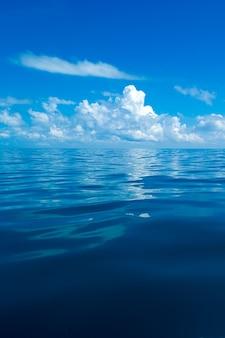 Wolken op blauwe lucht boven kalme zee met reflectie van zonlicht