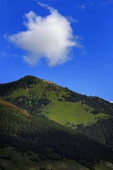 Wolken over de top van een rotsachtige berg