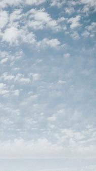 Wolken verspreid over de zomerhemel mobiel behang